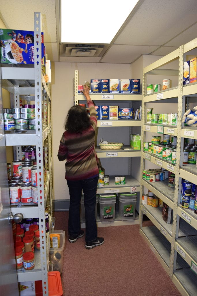 Volunteers help organize and stock the Food Pantry